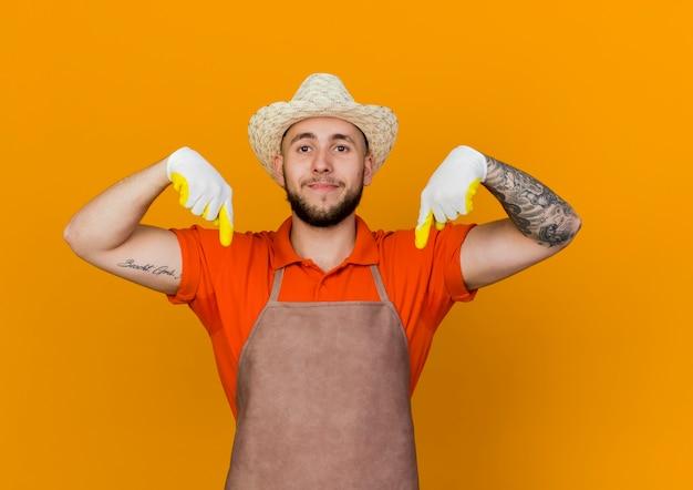 Heureux jardinier mâle portant chapeau et gants de jardinage pointe vers le bas avec deux mains