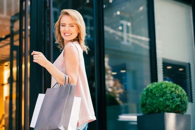 Heureux jeune adulte à l'extérieur avec des sacs à provisions souriant et clignant des yeux