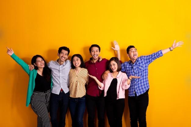Heureux jeune ami asiatique leva le bras ensemble