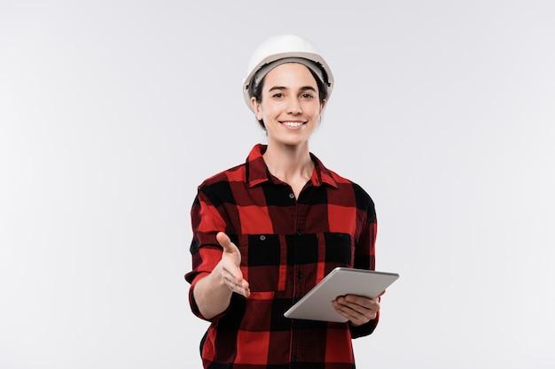 Heureux jeune architecte en casque et flanelle à l'aide du pavé tactile tout en vous accueillant par poignée de main devant la caméra en isolement