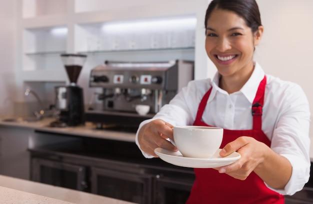 Heureux jeune barista offrant une tasse de café en souriant à la caméra
