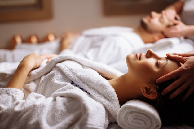 Heureux jeune beau couple profitant d'un massage de la tête au spa