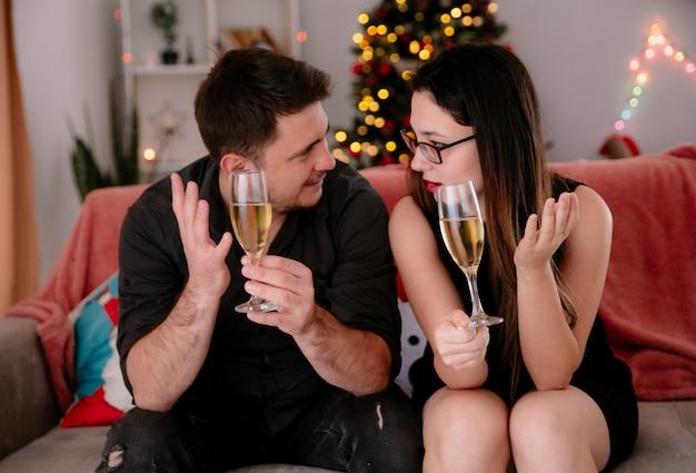 Heureux jeune et beau couple avec des verres de champagne est assis sur le canapé en se regardant dans une salle décorée de noël avec un arbre de noël en arrière-plan