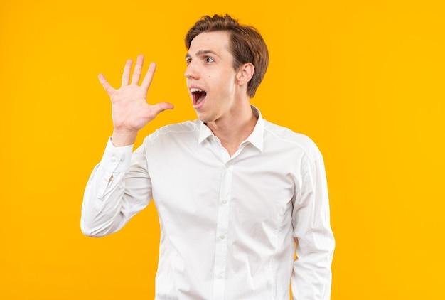 Heureux jeune beau mec vêtu d'une chemise blanche appelant quelqu'un isolé sur un mur orange