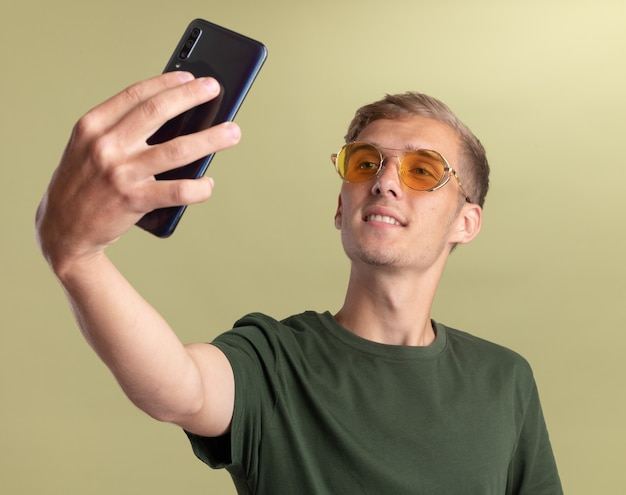 Heureux jeune beau mec vêtu d'une chemise verte avec des lunettes prend un selfie isolé sur un mur vert olive