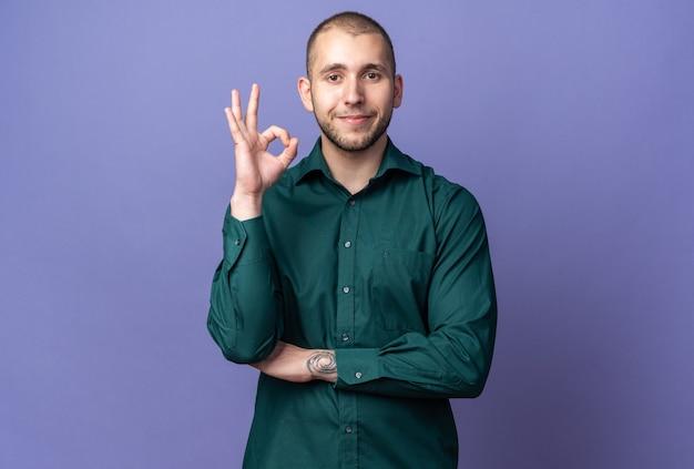 Heureux jeune beau mec vêtu d'une chemise verte montrant un geste correct