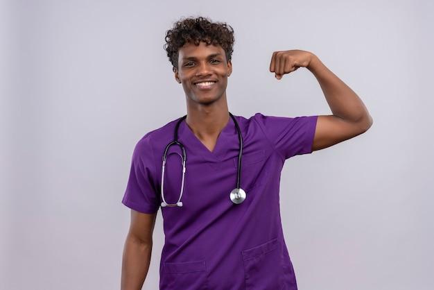Un heureux jeune beau médecin à la peau sombre avec des cheveux bouclés portant l'uniforme violet avec stéthoscope montrant le geste de force