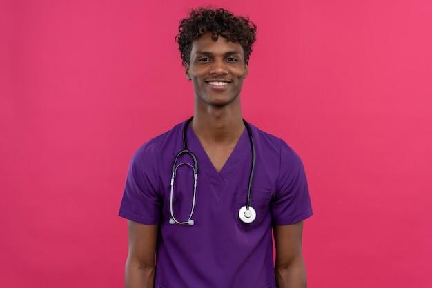 Un heureux jeune beau médecin à la peau sombre avec des cheveux bouclés portant l'uniforme violet avec stéthoscope en souriant tout