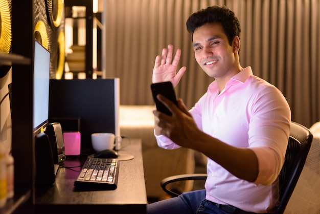 Heureux jeune bel homme d'affaires indien appel vidéo avec téléphone tout en travaillant des heures supplémentaires à la maison