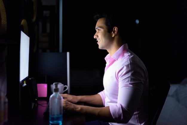 Heureux jeune bel homme d'affaires indien travaillant des heures supplémentaires à la maison pendant la quarantaine dans l'obscurité