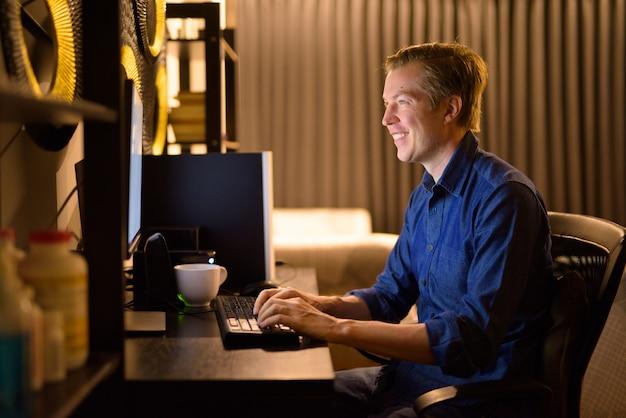 Heureux jeune bel homme d'affaires travaillant des heures supplémentaires à la maison tard dans la nuit