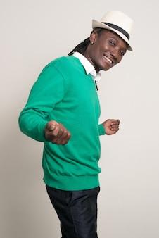 Heureux jeune bel homme africain avec chapeau dansant