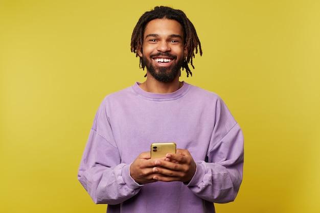 Heureux jeune bel homme aux cheveux brun avec des dreadlocks souriant joyeusement à la caméra tout en tenant un téléphone mobile, vêtu d'un sweat-shirt violet tout en étant isolé sur fond jaune