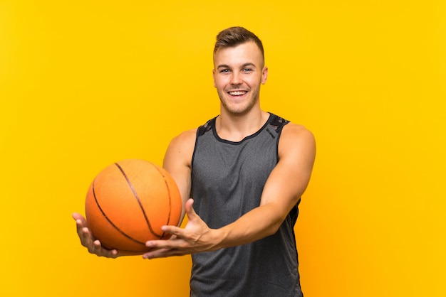 Heureux jeune bel homme blonde tenant un ballon de basket sur un mur jaune isolé