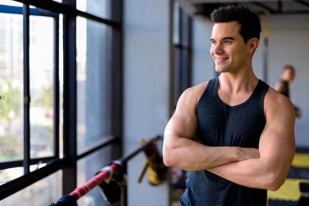 Heureux jeune bel homme pensant avec les bras croisés à la salle de gym
