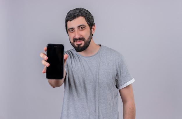 Heureux jeune bel homme qui s'étend de téléphone mobile isolé sur un mur blanc