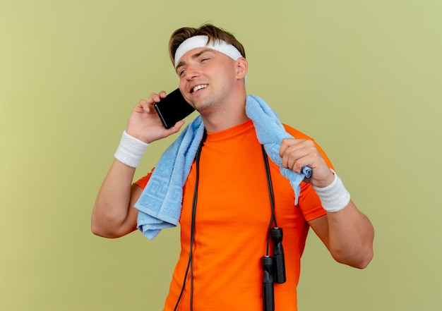 Heureux jeune bel homme sportif portant un bandeau et des bracelets avec une serviette et une corde à sauter autour du cou, parler au téléphone à la recherche droite et tenant une serviette isolée sur un mur vert olive