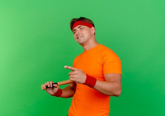 Heureux jeune bel homme sportif portant un bandeau et des bracelets tenant le baseball à la recherche et pointant droit chauve-souris isolé sur mur vert