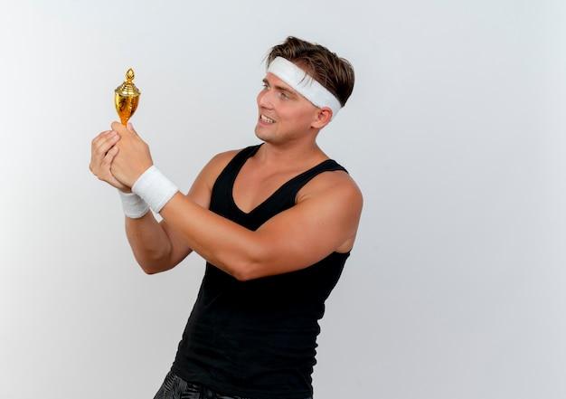 Heureux jeune bel homme sportif portant bandeau et bracelets tenant et regardant la coupe du gagnant isolé sur blanc avec espace copie