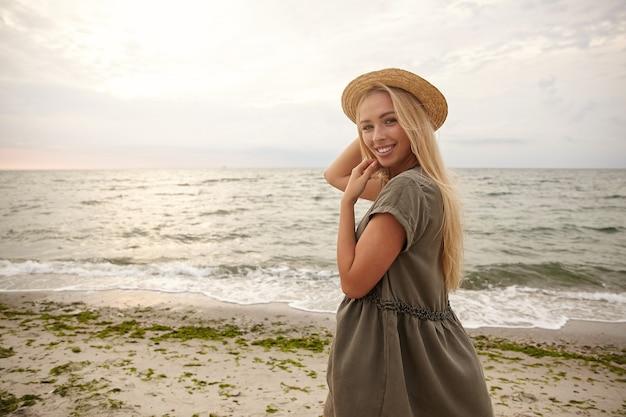Heureux jeune belle dame blonde aux cheveux longs en chapeau de bateau et robe d'été souriant joyeusement tout en regardant positivement par-dessus son épaule, isolé sur fond de plage