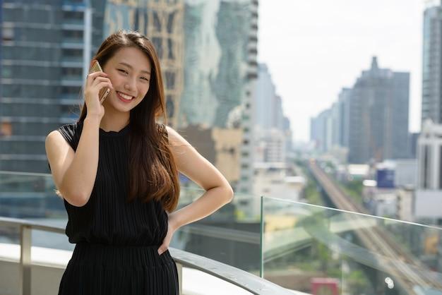 Heureux jeune belle femme d'affaires asiatique parlant au téléphone contre vue sur la ville