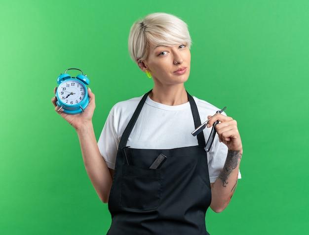Heureux jeune belle femme barbier en uniforme tenant un réveil avec un rasoir droit isolé sur un mur vert