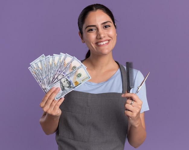 Heureux jeune belle femme coiffeur en tablier tenant de l'argent et des ciseaux avec un peigne à l'avant avec le sourire sur le visage debout sur le mur violet