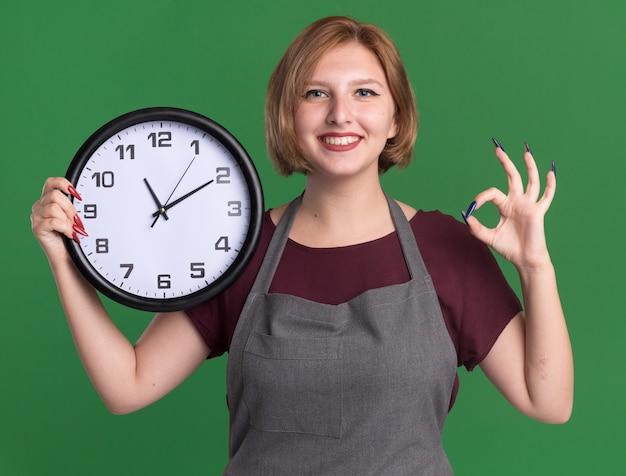 Heureux jeune belle femme coiffeur en tablier tenant horloge murale regardant à l'avant avec sourire montrant signe ok debout sur mur vert