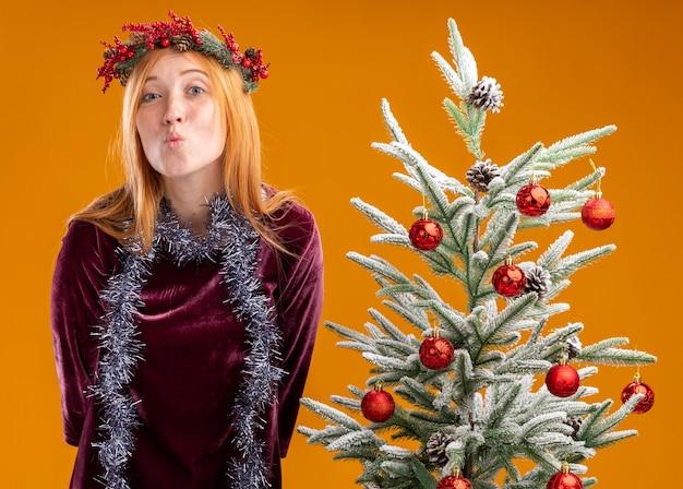 Heureux jeune belle fille debout à proximité de l'arbre de noël portant robe rouge et couronne avec guirlande sur le cou montrant le geste de baiser isolé sur fond orange