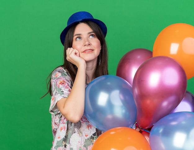 Heureux jeune belle fille portant un chapeau de fête tenant des ballons mettant le poing sur la joue