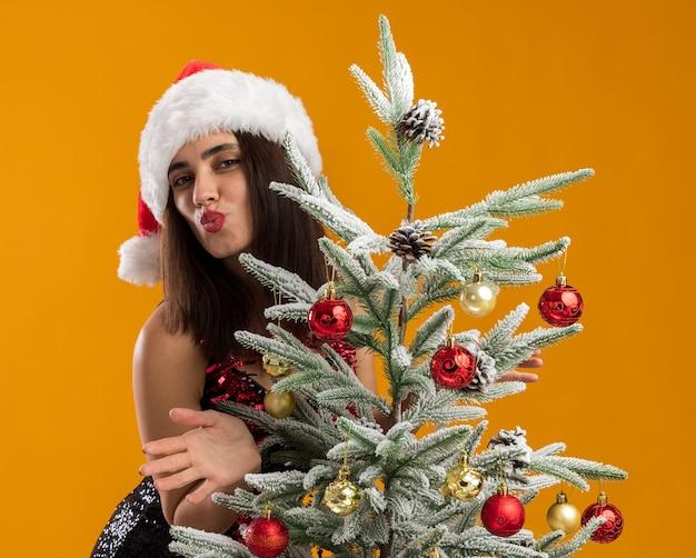 Heureux jeune belle fille portant un chapeau de noël avec guirlande sur le cou debout derrière l'arbre de noël montrant le geste de baiser isolé sur fond orange