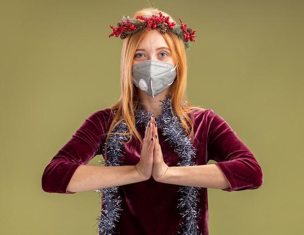Heureux jeune belle fille vêtue d'une robe rouge avec couronne et masque médical avec guirlande sur le cou montrant le geste de prier isolé sur fond vert olive