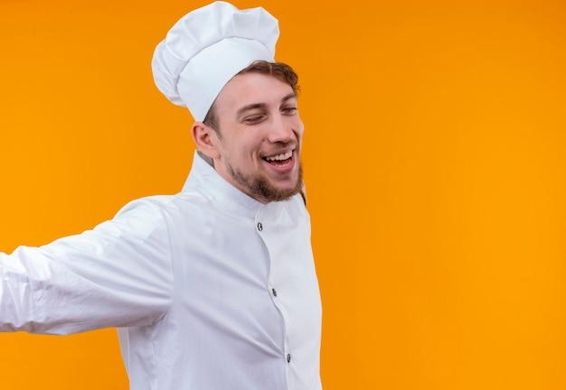 Un heureux jeune chef barbu homme en uniforme blanc ouvrant largement ses bras avec les yeux fermés sur un mur orange