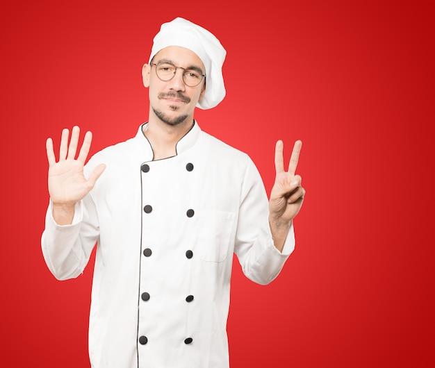 Heureux jeune chef faisant un geste numéro sept avec ses mains