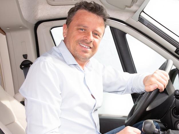 Heureux jeune conducteur de voiture derrière le volant du concept de conduite de van