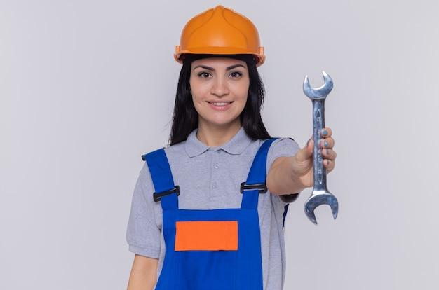 Heureux jeune constructeur femme en uniforme de construction et casque de sécurité tenant la clé à l'avant souriant confiant debout sur mur blanc