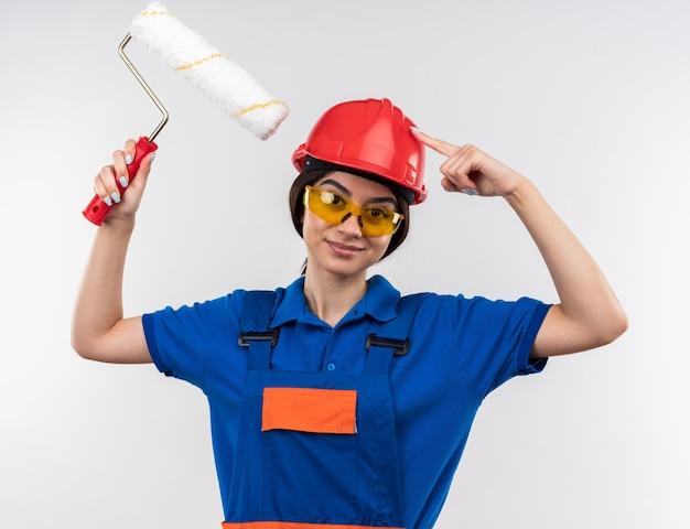Heureux jeune constructeur femme en uniforme avec des lunettes tenant une brosse à rouleau mettant le doigt sur la tête