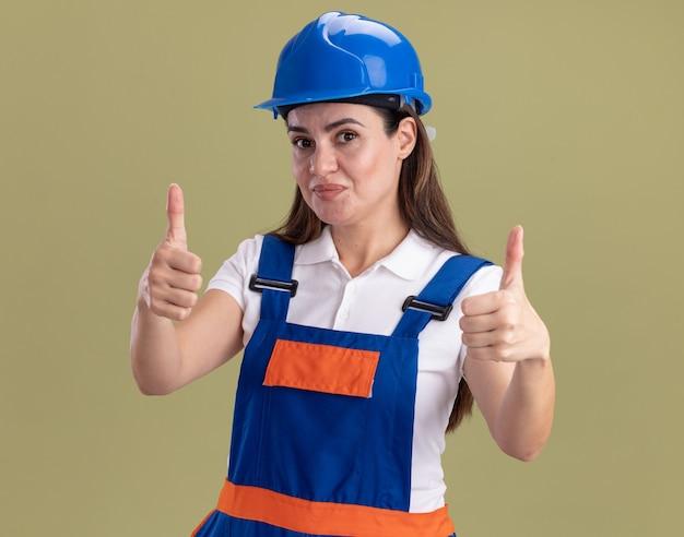 Heureux jeune constructeur femme en uniforme montrant les pouces vers le haut isolé sur mur vert olive