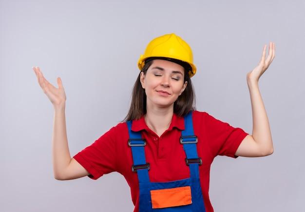 Heureux jeune constructeur fille lève les mains avec les yeux fermés sur fond blanc isolé