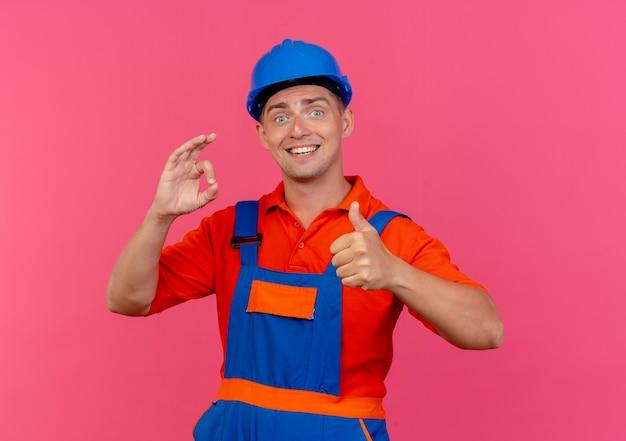 Heureux jeune constructeur de sexe masculin portant l'uniforme et un casque de sécurité montrant un geste okey son pouce vers le haut sur rose