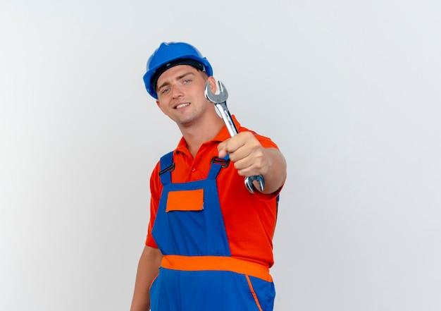 Heureux jeune constructeur de sexe masculin portant l'uniforme et un casque de sécurité tenant une clé à la caméra sur blanc