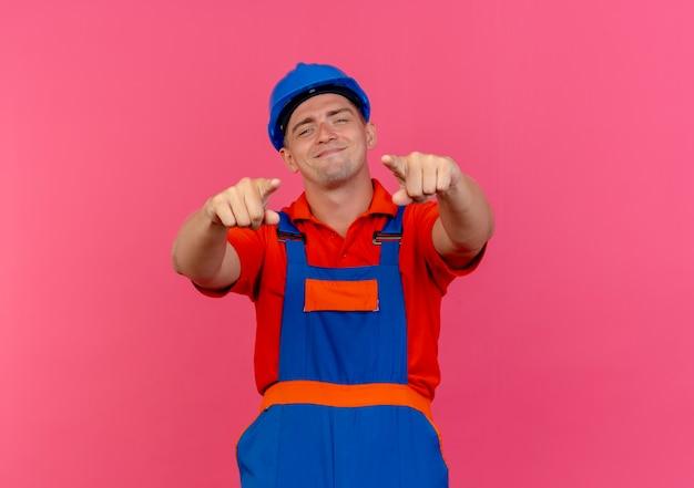 Heureux jeune constructeur de sexe masculin portant l'uniforme et les points de casque de sécurité à la caméra sur rose
