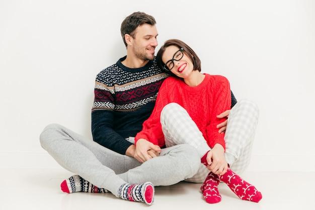 Heureux jeune copine et petit ami porte un chandail et des chaussettes chaudes, assis près de l'autre sur le sol blanc
