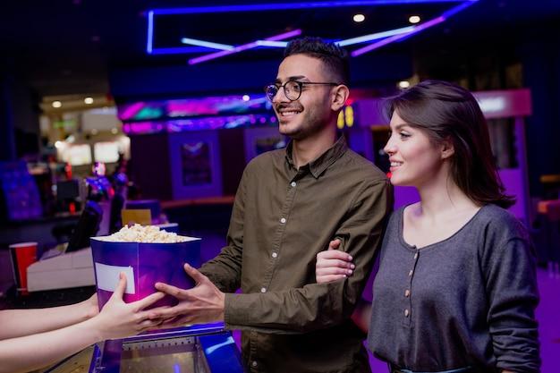 Heureux jeune couple affectueux achetant du pop-corn et des billets au cinéma tout en allant regarder un film
