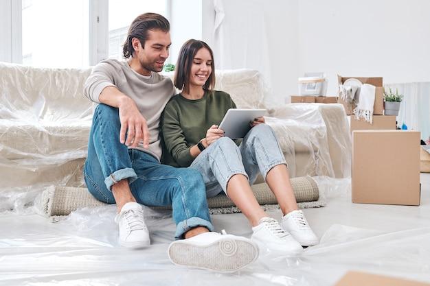 Heureux Jeune Couple Affectueux Assis Sur Le Sol Du Salon De Leur Nouvel Appartement Ou Maison Et Faire Défiler Les Meubles En Ligne Photo Premium