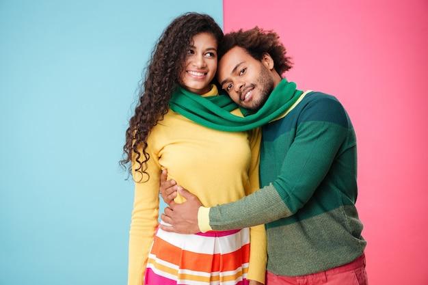 Heureux jeune couple africain en écharpe debout et étreignant