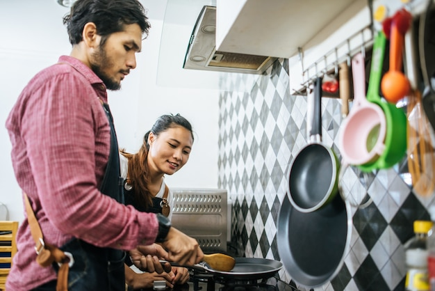 Heureux jeune couple aidant les uns les autres cuisine dans la cuisine à la maison.