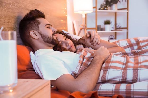 Heureux jeune couple allongé dans son lit la nuit