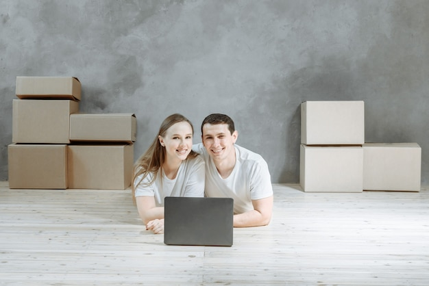 Heureux jeune couple allongé sur le sol près des boîtes de déménagement dans l'appartement. t