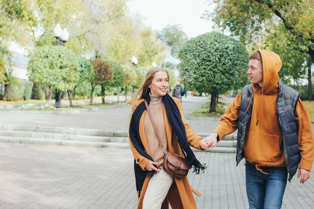 Heureux jeune couple amoureux amis adolescents habillés dans un style décontracté marchant ensemble dans la rue de la ville